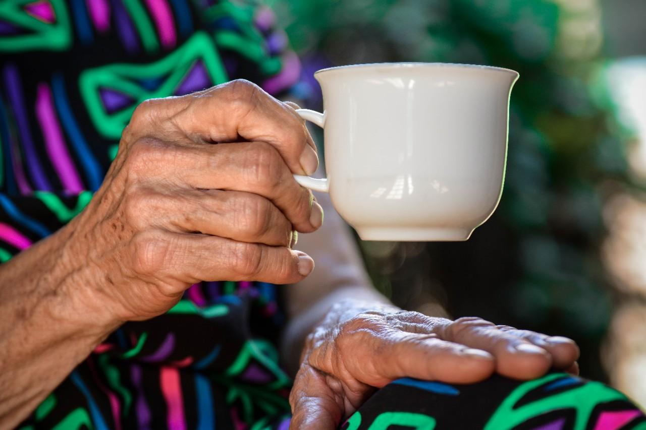 A hand holds a teacup.