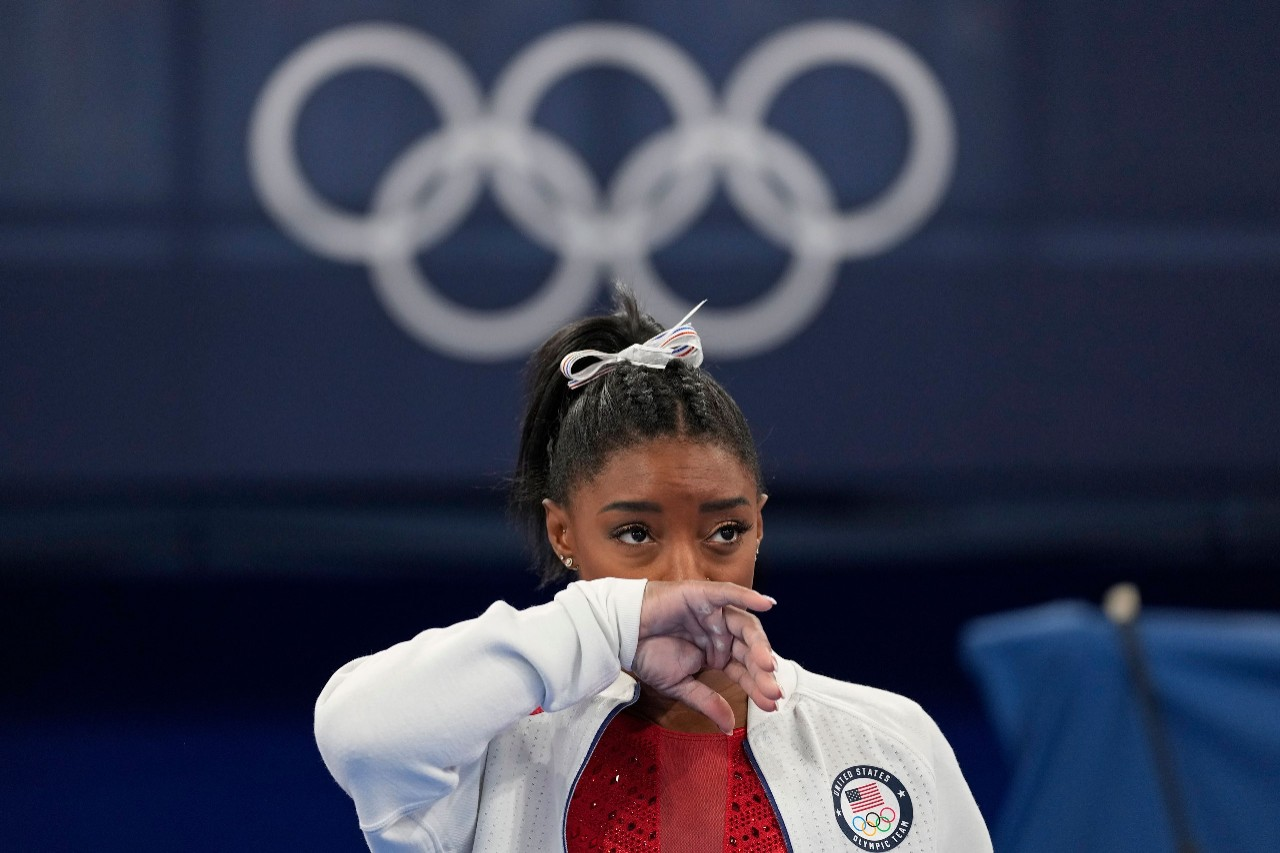 gymnast simone biles standing in front of the olympic rings