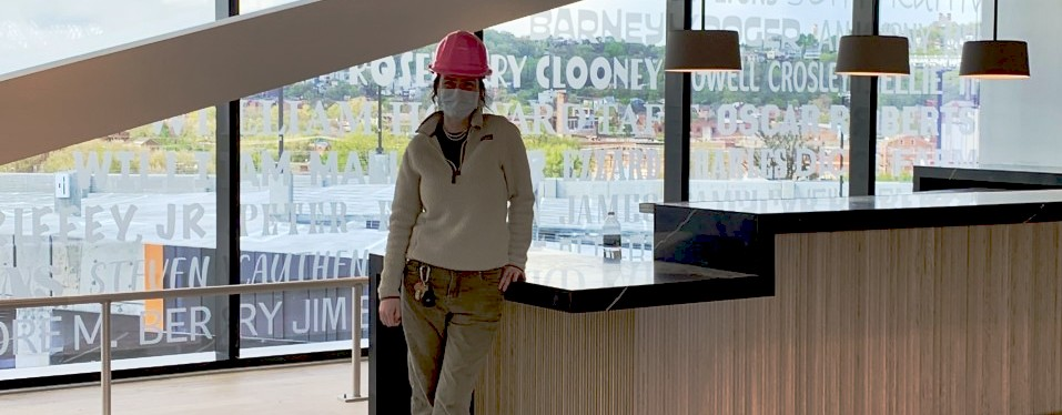 UC DAAP student Emily Baxter stands inside a Cincinnati's FC Stadium clubhouse wearing a PPE mask