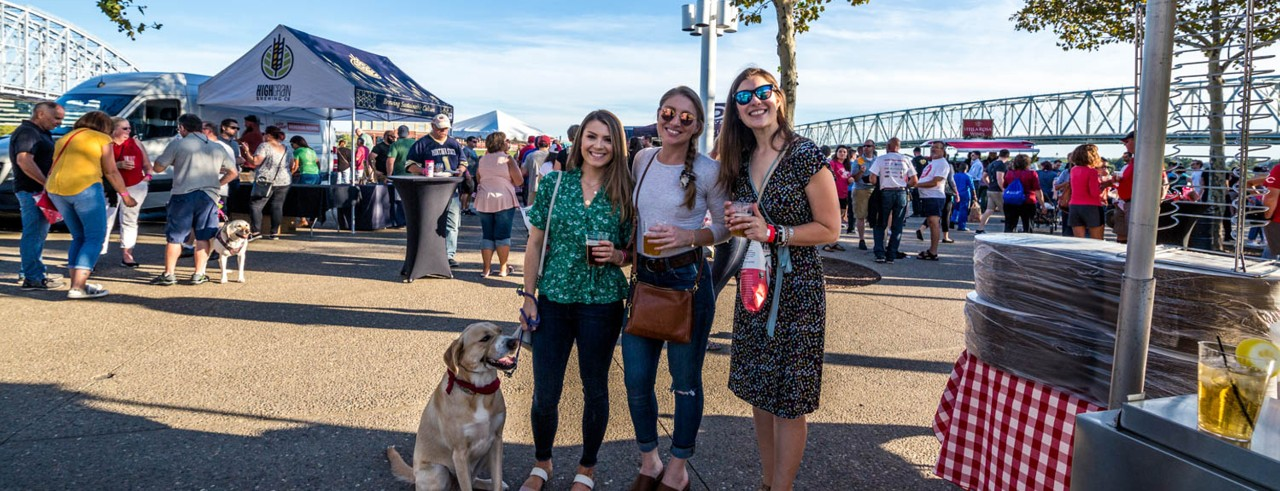 three young women and dog at outside event