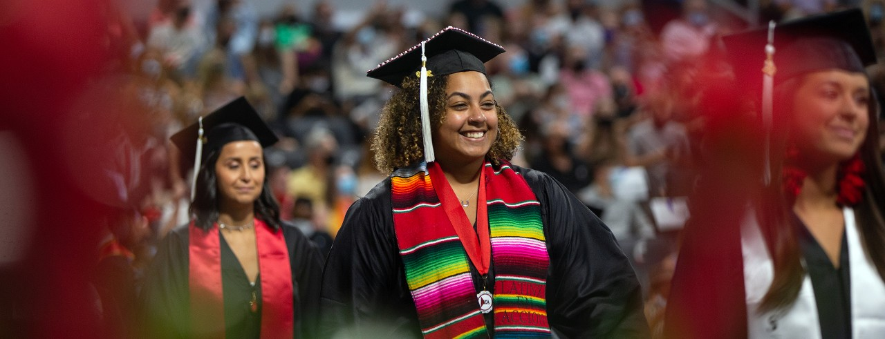 A UC grad takes part in Commencement at Fifth Third Arena.