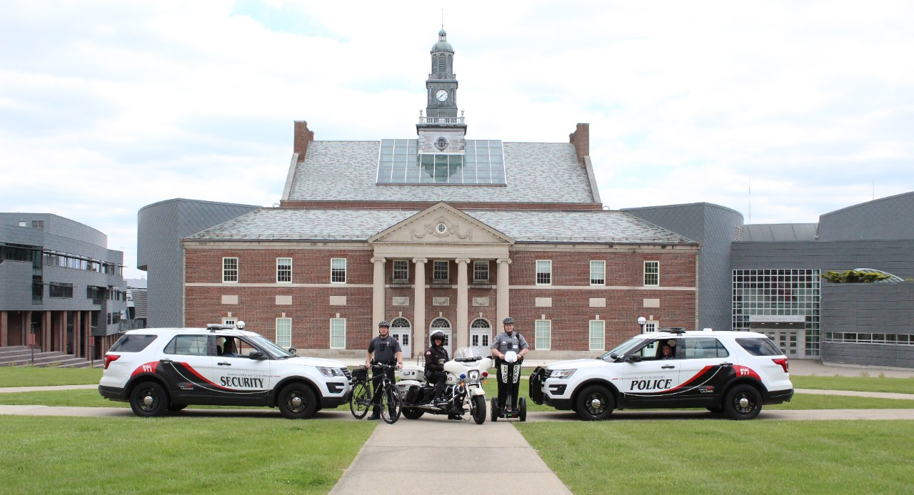 UCPD cruisers sit in front of TUC with a bicycle, segway and motorcycle.
