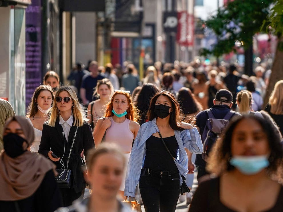 Photo shows people walking on a city sidewalk