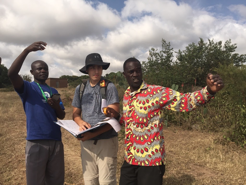 A student with two community members in Tanzania