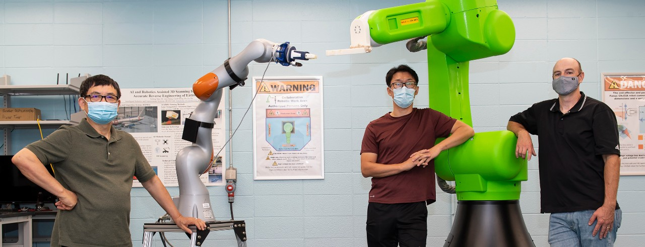 Ou Ma, Yufeng Sun and Andrew Barth pose in face masks in front of two robotic arms in an engineering lab.