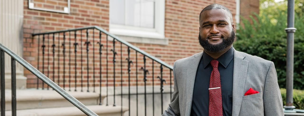 Damon Davis wearing gray jacket, red tie in front of University of Cincinnati building