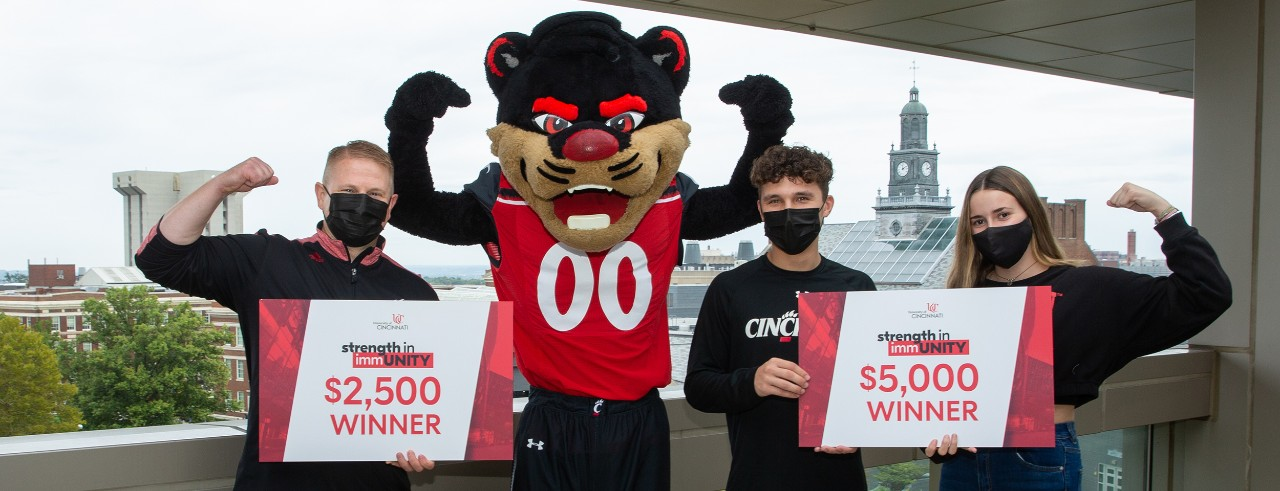 Three people in masks pose with Bearcat mascot