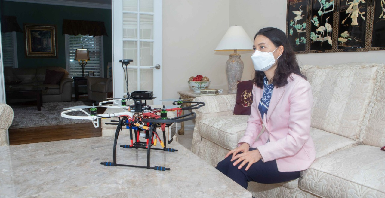A woman in a face mask sits on a couch in front of a drone sitting on a coffee table in front of her.