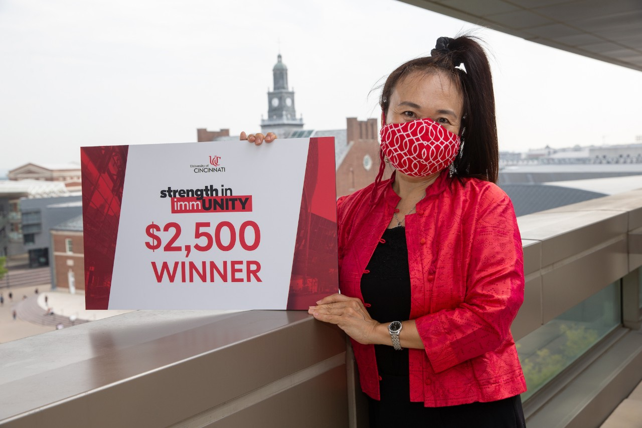 Woman holds sign indicating winning $2500