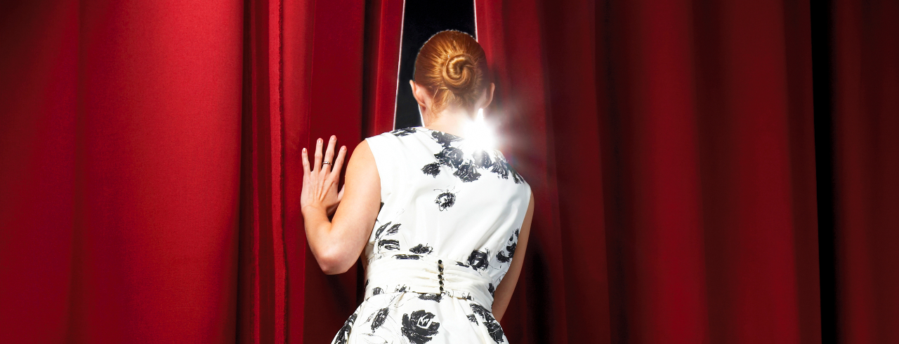 A girl peeks behind a red stage curtain.