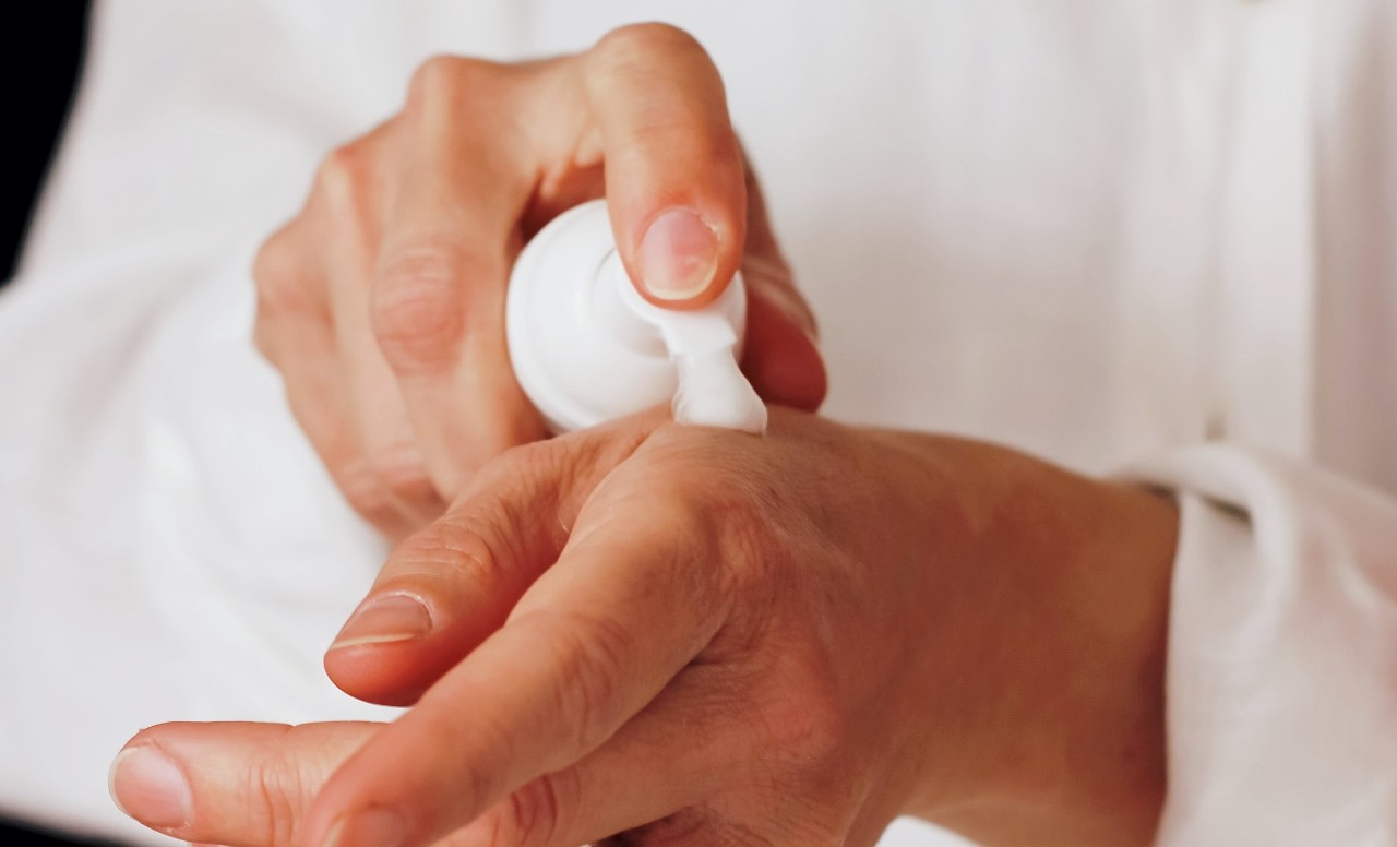lotion being dispensed from bottle by male hands onto skin of his hands