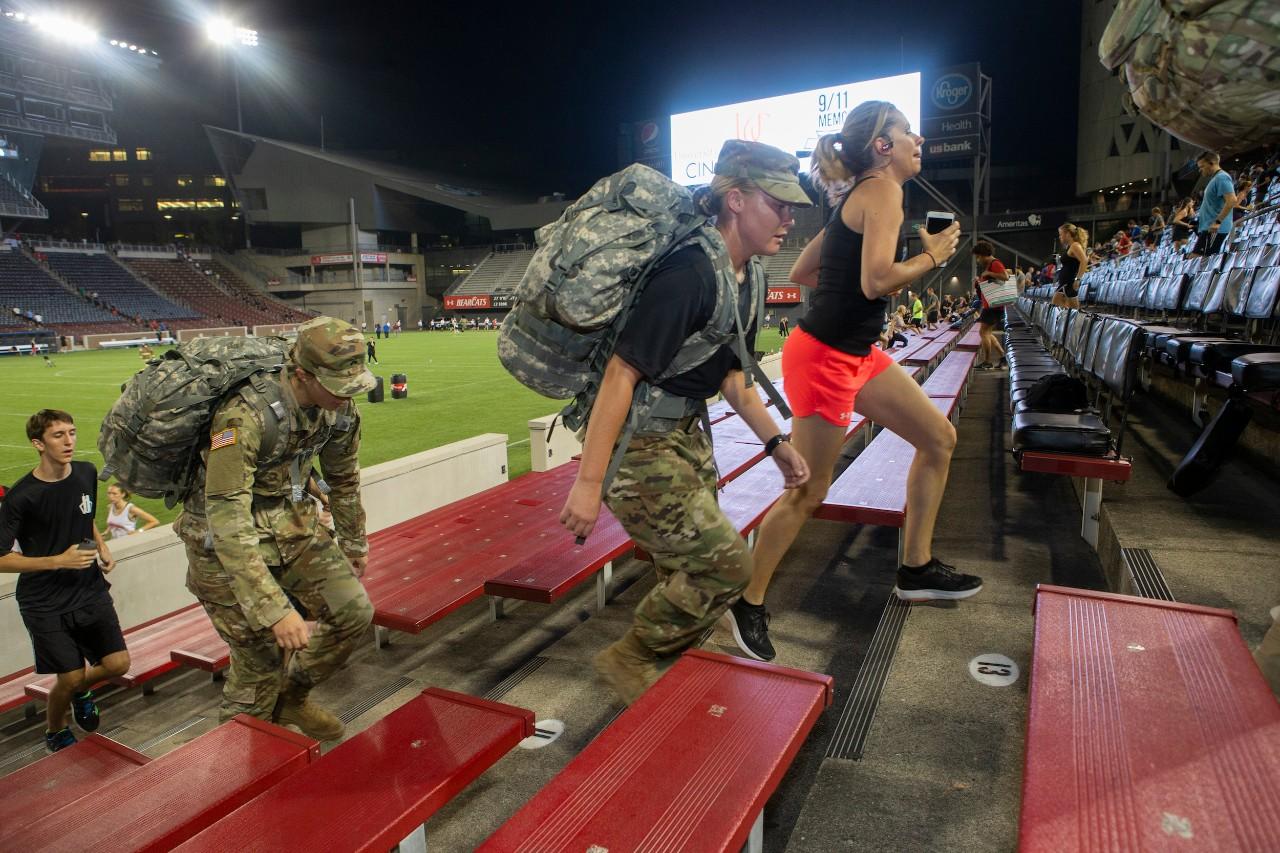 Members of UC's ROTC climb the steps at Nippert Stadium.