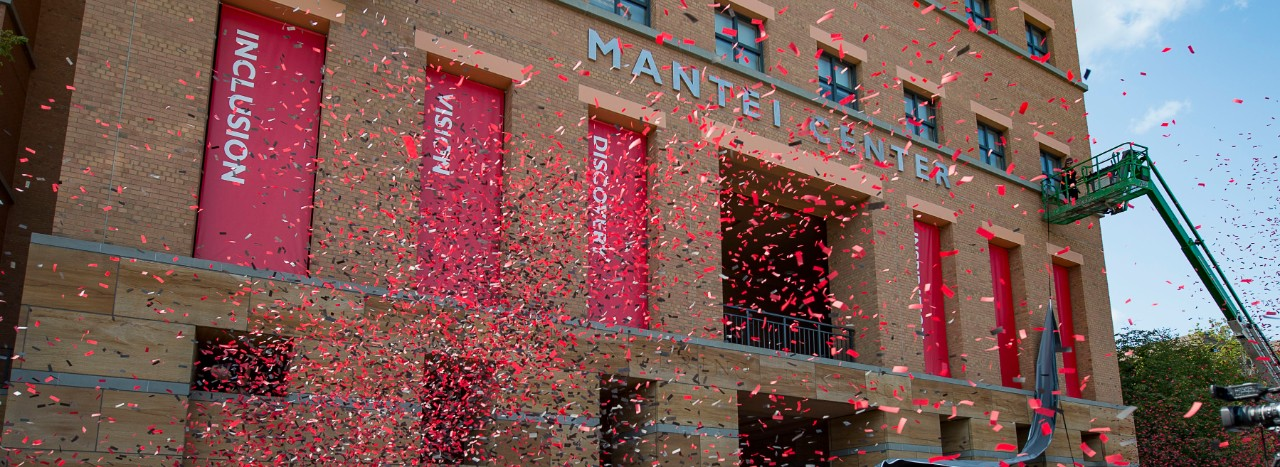 Dedication of Mantei Center on UC's campus. Red confetti in front of building.