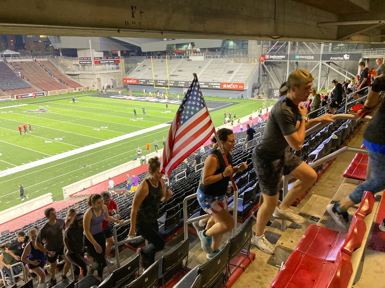 Students including one carrying an American flag run the steps of Nippert Stadium.