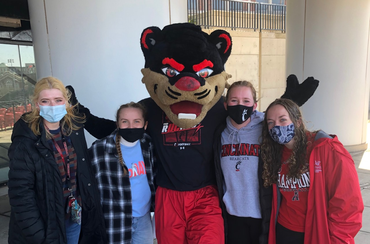Students posing with the Bearcat mascot
