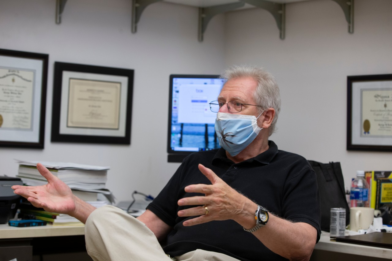 George Uetz wearing a face mask with a spider on the front talks in his office.