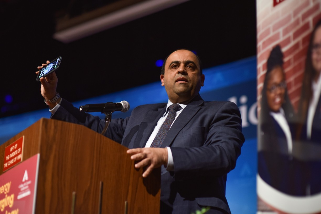 Hazem Said holds up a cell phone at a podium while giving a talk.