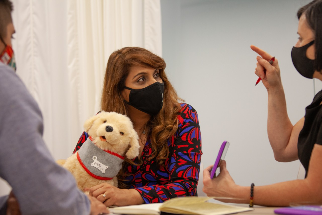 Woman holding robot puppy talks with two researchers