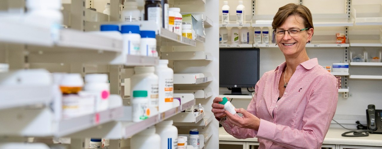 UC pharmacy professor Bethanne Brown stand among medications in a pharmacy