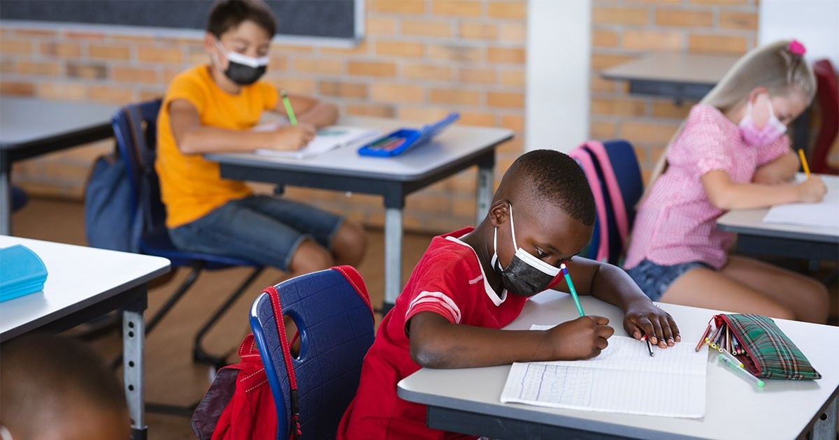 students in class wearing masks while seated at their desks