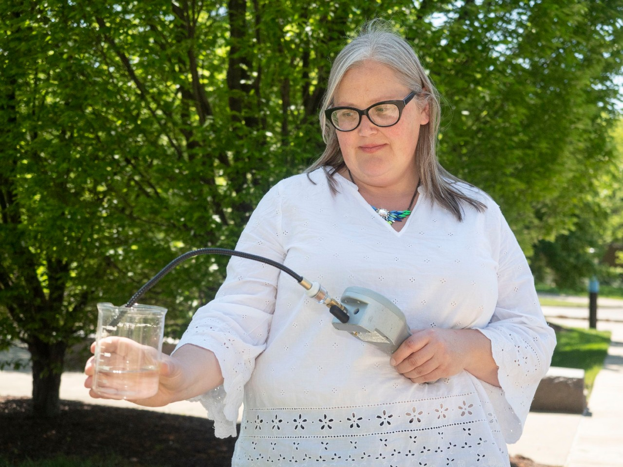 UC associate professor Amy Townsend-Small samples methane in a beaker of water.