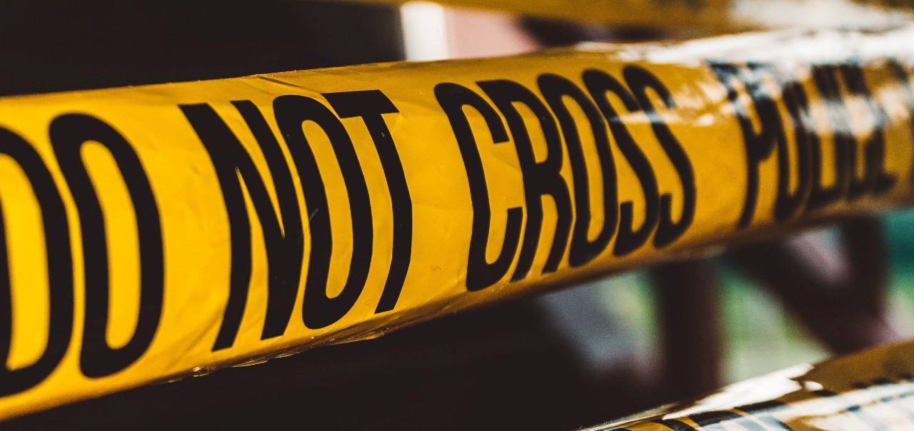 yellow crime tape saying Do Not Cross Police