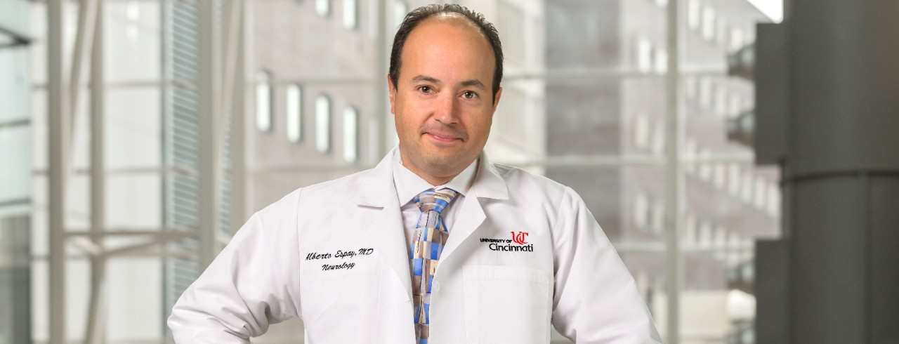 Alberto Espay wearing a white lab coat and standing in the UC College of Medicine lobby
