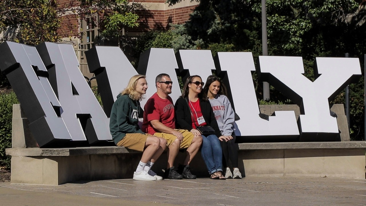 family members seated in front of a sign reading family on the UC campus