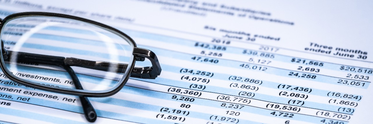 Stock image of a profit and loss sheet with glasses folded up on top.