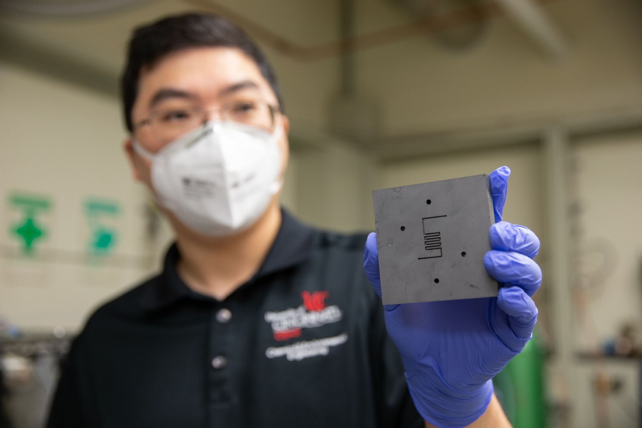 Wearing a face mask and rubber gloves, Jingjie Wu holds up catalyst reactor in a lab.