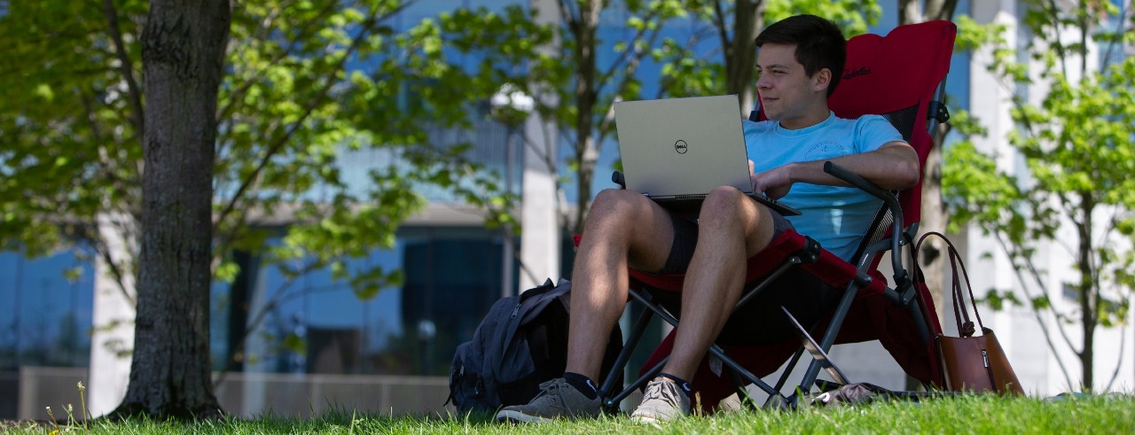 A student works on a laptop in the shade of a tree.
