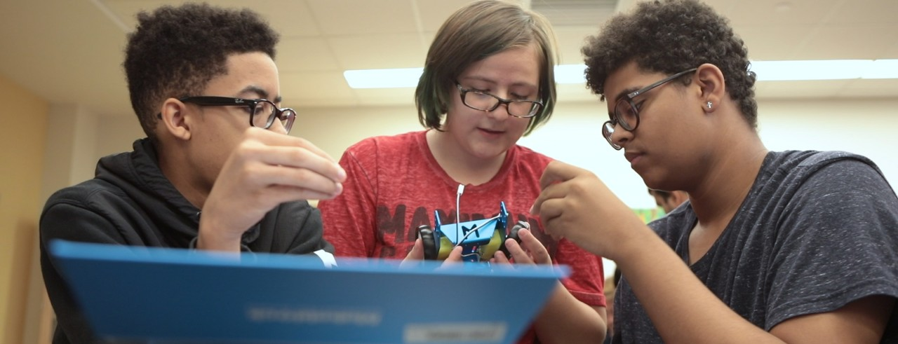 High school students collaborate on a robotics project.