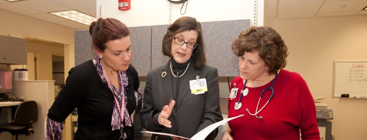 Three women discuss a patient case file