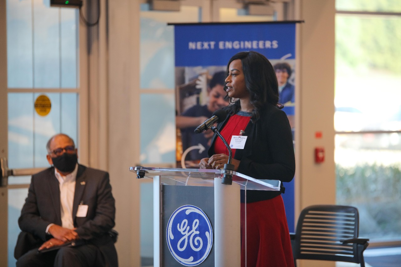 Whitney Gaskins speaks at a podium at GE Aviation's Learning Center.
