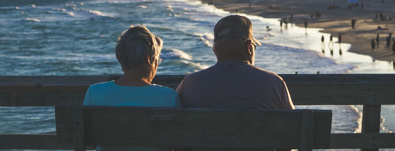 An elderly couple sits on a bench looking out at a body of water